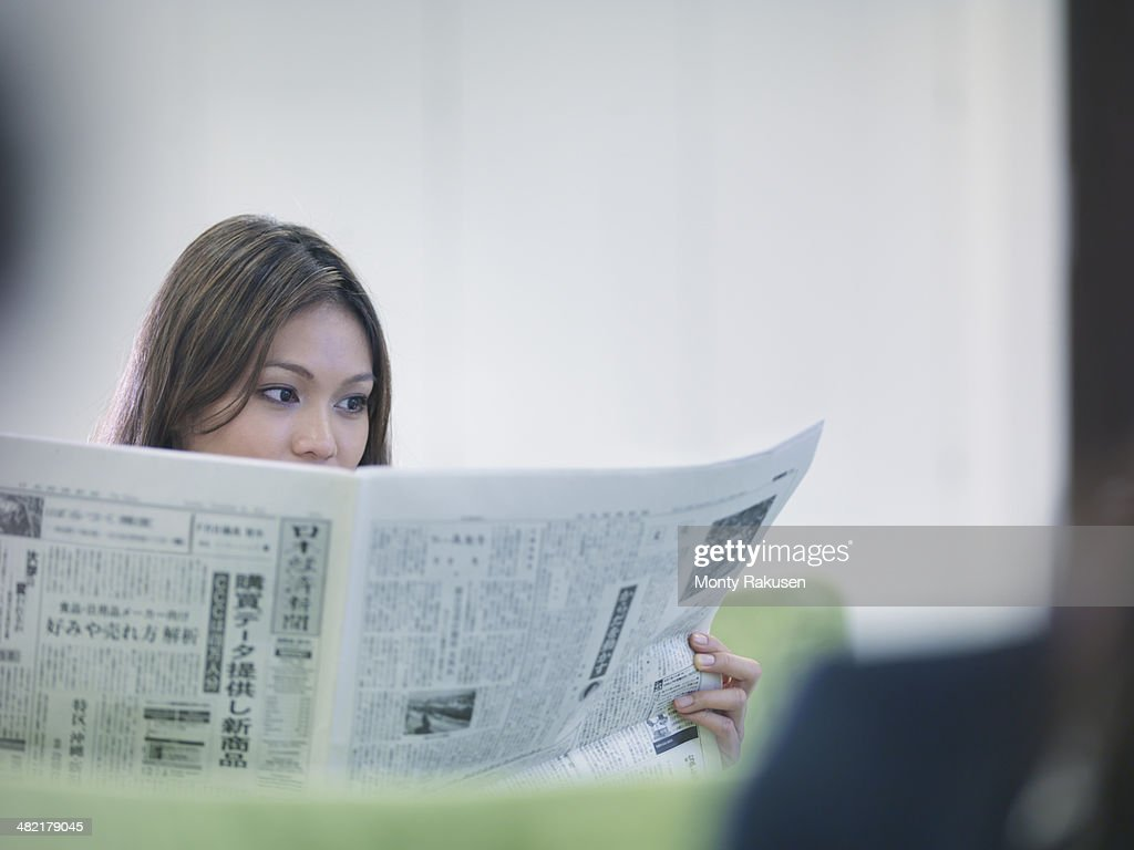 Businesswoman reading Japanese newspaper : Stock Photo