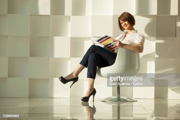 Businesswoman Reading Magazine While Sitting In Chair Against White Modern Wall