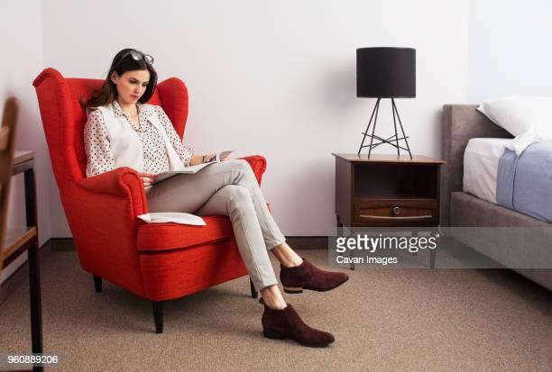 businesswoman reading magazine while sitting on red armchair in hotel room - sessel stock-fotos und bilder