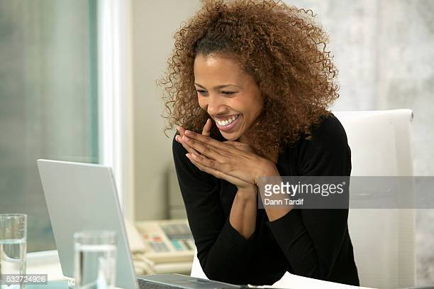 Businesswoman Reading Message on Laptop