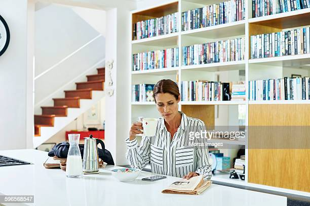 businesswoman reading newspaper at home - routine stock-fotos und bilder