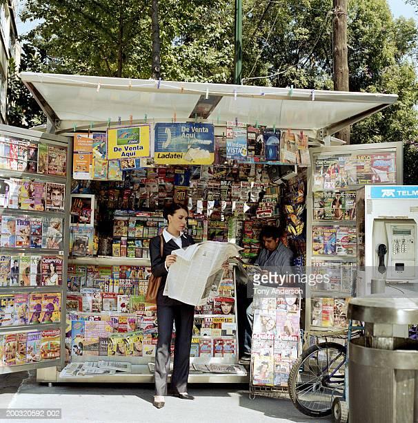 Businesswoman reading newspaper at kiosk