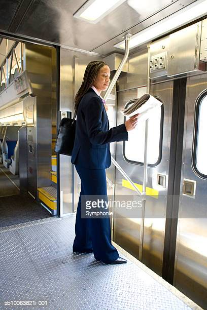 Businesswoman reading newspaper commuting on train
