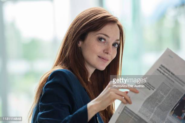 businesswoman reading newspaper in hotel - routine stock pictures, royalty-free photos & images