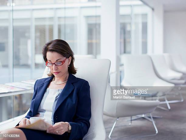 Businesswoman reading newspaper in waiting area