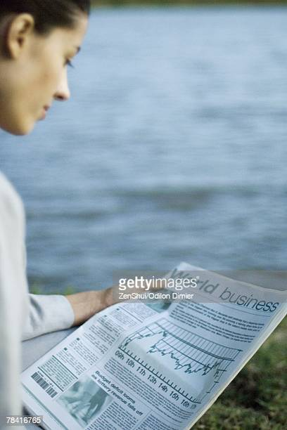 Businesswoman reading newspaper, lake in background