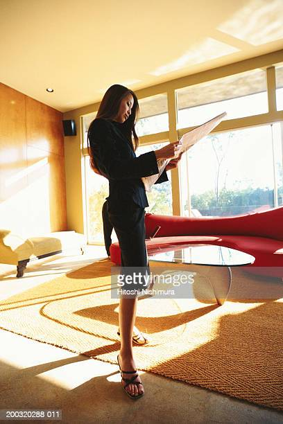 businesswoman reading newspaper, low angle view - black skirt stock photos and pictures