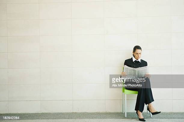 Businesswoman reading newspaper outdoors