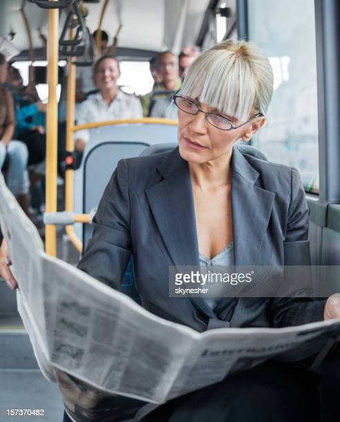 Femme d'affaires lire des journaux dans le bus.