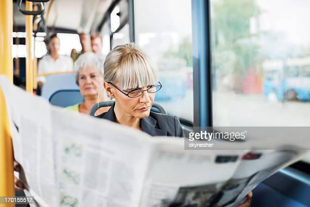 Geschäftsfrau lesen Zeitung auf dem bus.