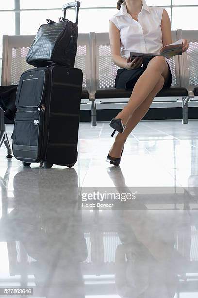 Businesswoman Reading on an Airport Bench