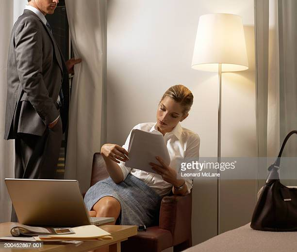 Businesswoman reading paperwork, businessman standing by window