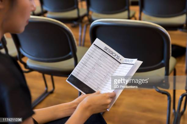 businesswoman reading schedule during conference - pamphlet stock pictures, royalty-free photos & images