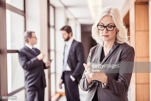 Businesswoman reading smartphone update in office corridor