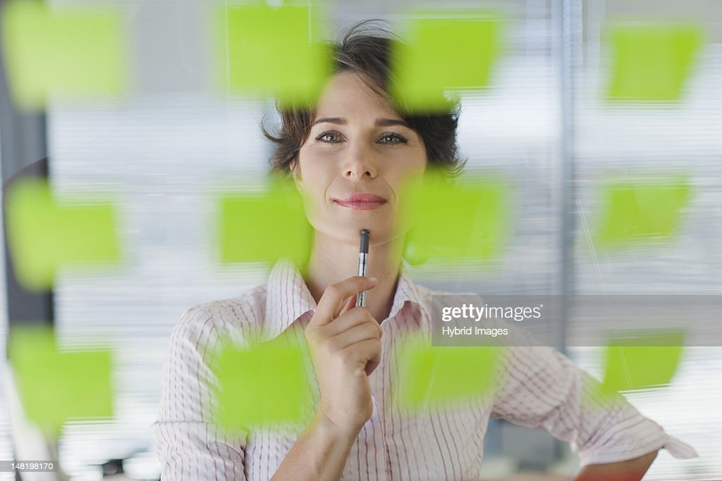 Businesswoman reading sticky notes : Stock Photo