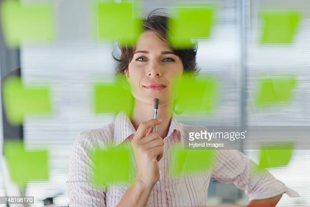 Businesswoman reading sticky notes