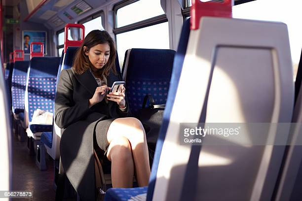 Businesswoman Reading Text Message On Train During Commute
