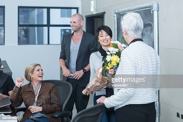 Businesswoman receiving bunch of flowers on a casual meeting