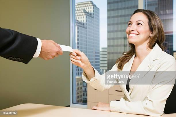 businesswoman receiving business card - solapa papel fotografías e imágenes de stock