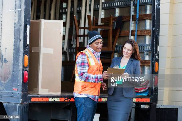 businesswoman receiving delivery, signing a clipboard - loading dock stock pictures, royalty-free photos & images