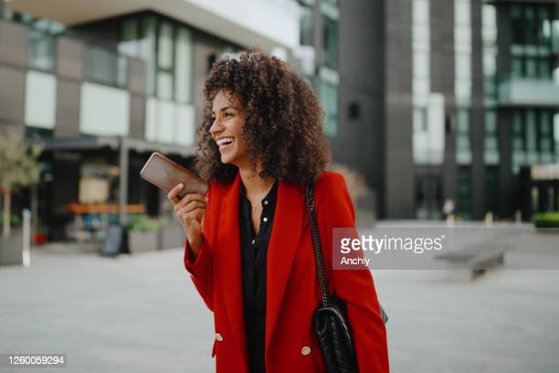 businesswoman recording voice message using her smartphone - red stock pictures, royalty-free photos & images