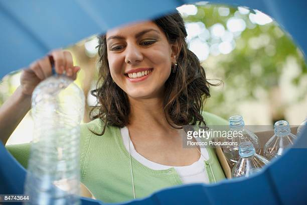 Businesswoman recycling water bottles