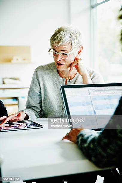 Businesswoman referencing data on digital tablet