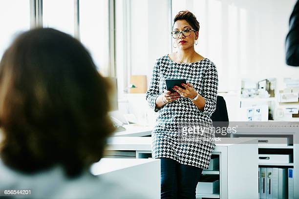 Businesswoman referencing digital tablet in office