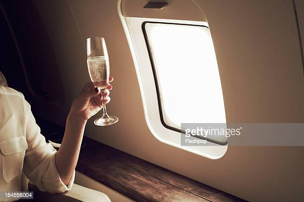 businesswoman relaxing aboard private jet - geschäftsreise stock-fotos und bilder