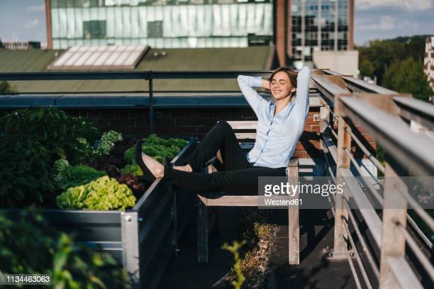 businesswoman relaxing in his urban rooftop garden - ruhen stock-fotos und bilder