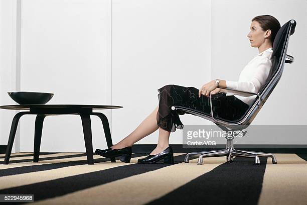 businesswoman relaxing in modern office - vcg stock pictures, royalty-free photos & images