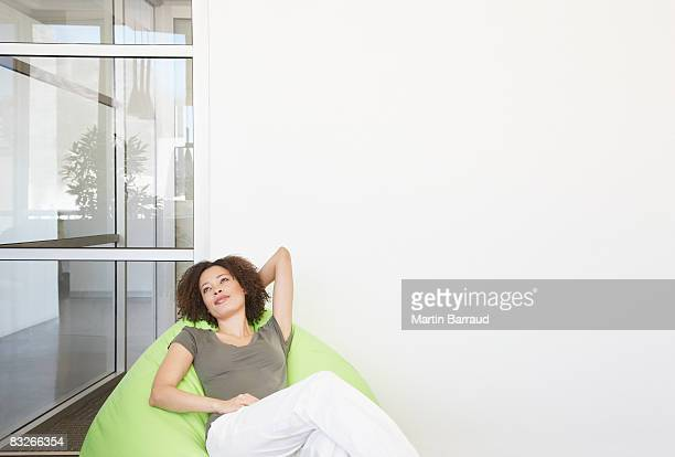 businesswoman relaxing in office beanbag chair - one mid adult woman only stock pictures, royalty-free photos & images