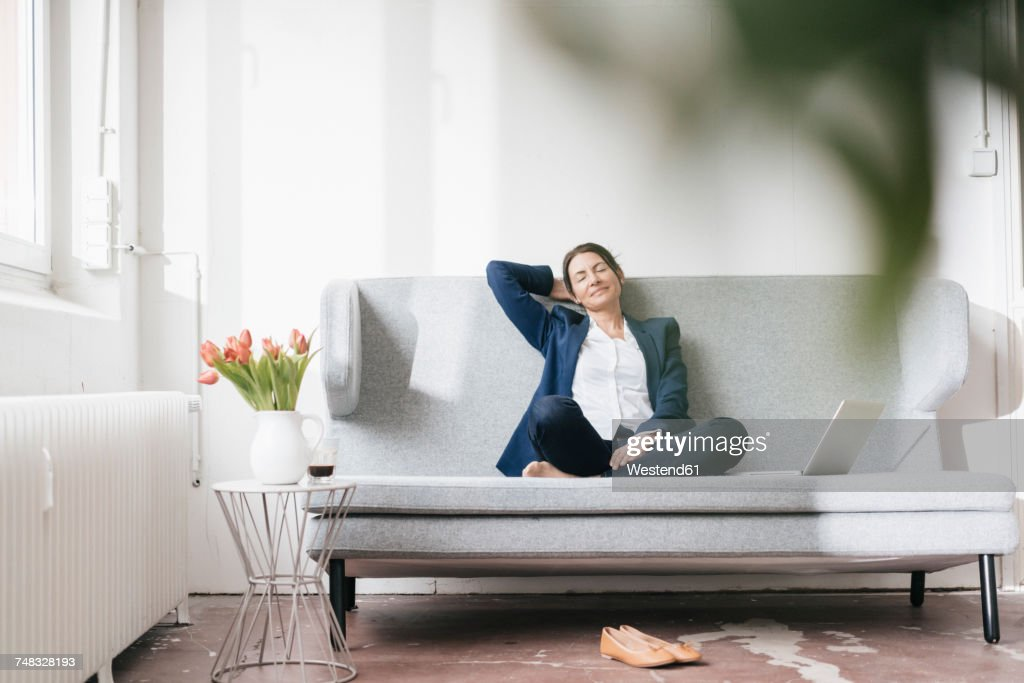 Businesswoman relaxing on couch in a loft : Stock-Foto