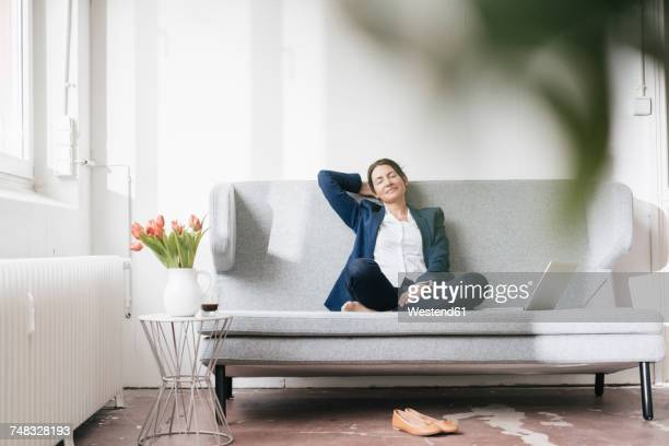Businesswoman relaxing on couch in a loft