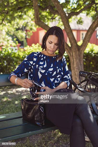 Businesswoman removing in-ear headphones from purse while sitting on park bench