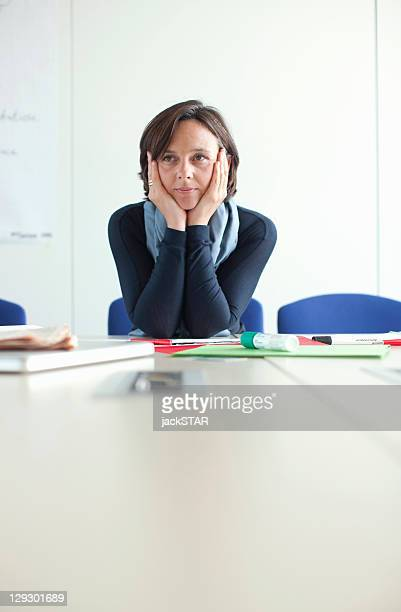 Businesswoman resting chin in hands