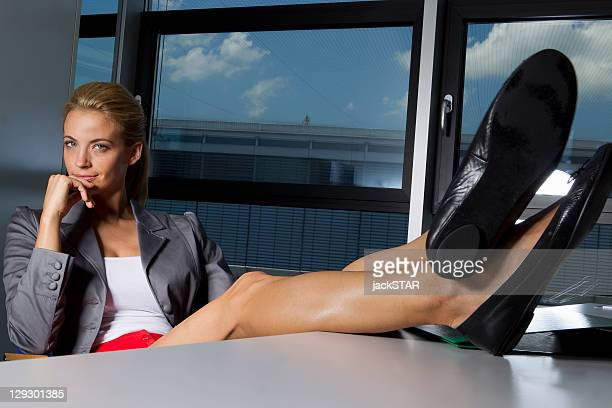 Donna d'affari di riposo piedi sulla scrivania