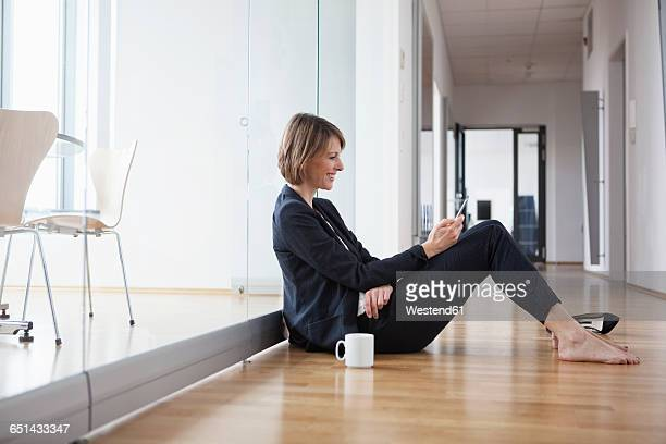 Businesswoman resting on office floor looking at cell phone