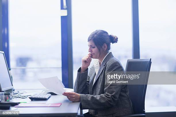 businesswoman reviewing paperwork at desk in office, freiburg im breisgau, baden-w��rttemberg, germany - sigrid gombert stock pictures, royalty-free photos & images