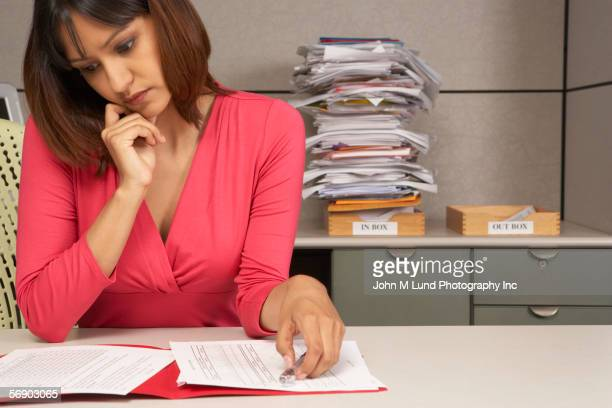 Businesswoman reviewing paperwork at desk