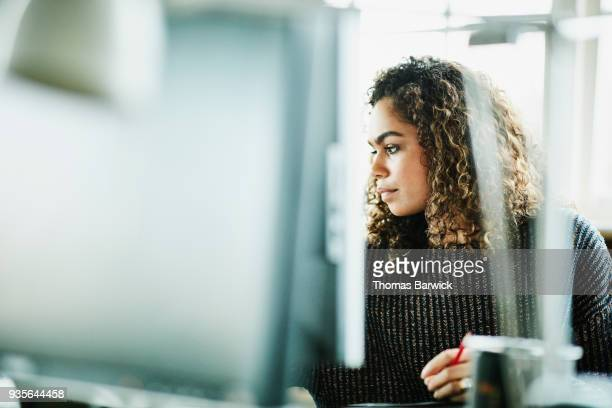 businesswoman reviewing project on computer monitor at workstation in office - truth or dare stock pictures, royalty-free photos & images