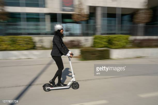 businesswoman riding an electric push scooter through the city - electric scooter stock pictures, royalty-free photos & images
