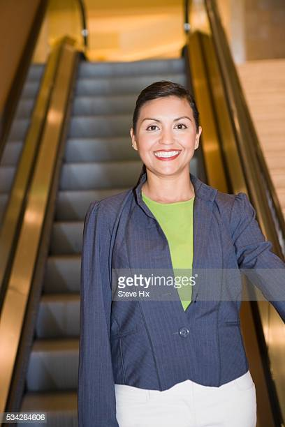 businesswoman riding an escalator - down blouse stock pictures, royalty-free photos & images