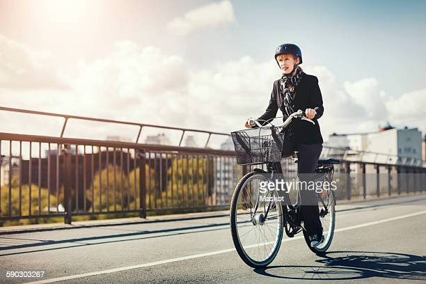 Businesswoman riding bicycle on bridge in city
