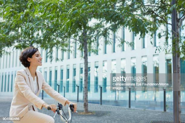 Businesswoman riding bicycle on city street