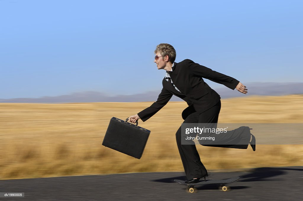 Businesswoman Riding on a Skateboard and Holding a Briefcase : Stock Photo
