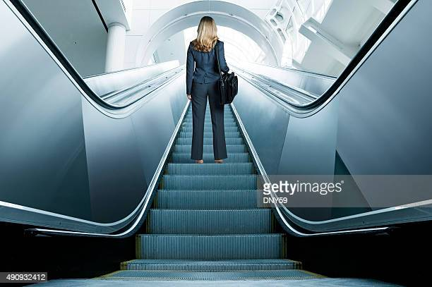 Businesswoman Riding Up An Escalator