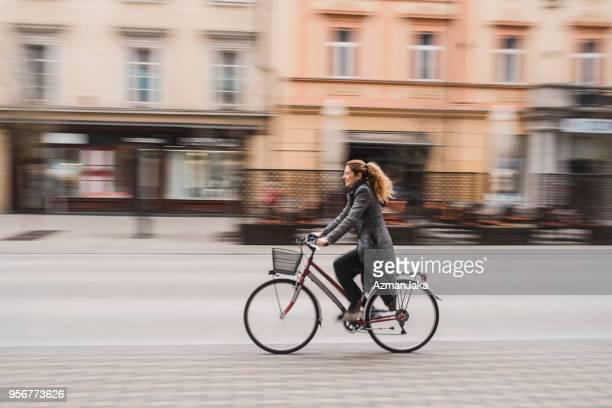 businesswoman riding with a bike in the city - bicicletta foto e immagini stock