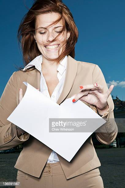 Businesswoman ripping paper outdoors