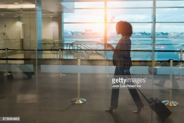 Businesswoman rolling luggage in airport waiting area